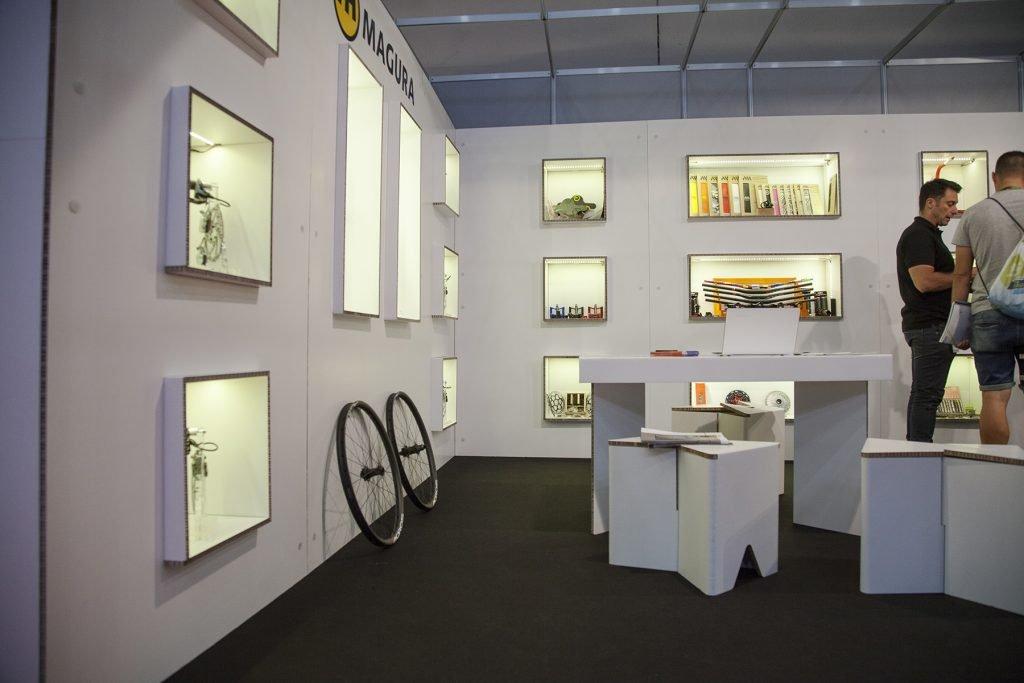 Stand de cartón con sistema de pared doble y estantería con cubos e iluminación